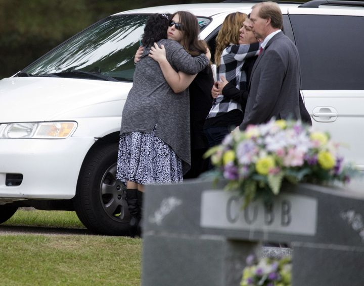 Mourners, believed to be family members, embrace as they gather for the burial of six-year old Jeremy Mardis at a cemetery in