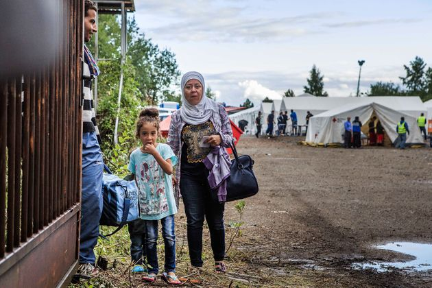 A refugee family waits on a gate inside a temporary tent camp on July 27, 2015 in Dresden,
