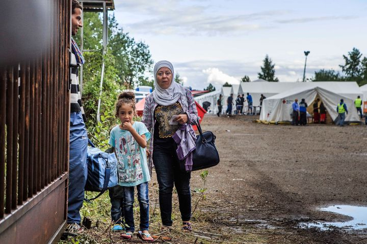 A refugee family waits on a gate inside a temporary tent camp on July 27, 2015 in Dresden, Germany.