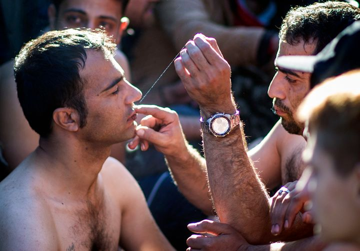 A man sews shut the mouth of a fellow migrant from Iran as migrants and refugees wait to cross the Greek-Macedonian border ne