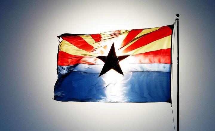 The setting sun illuminates the state flag of Arizona in this undated Getty file photo.