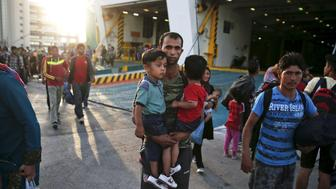 An Afghan refugee holds his two sons following her arrival onboard the Eleftherios Venizelos passenger ship at the port of Piraeus, near Athens, Greece September 7, 2015. Greece is struggling to cope with the hundreds of migrants and refugees from the war in Syria making the short crossing every day from Turkey to Greece's eastern islands, including Kos, Lesbos, Samos and Agathonisi. REUTERS/Alkis Konstantinidis