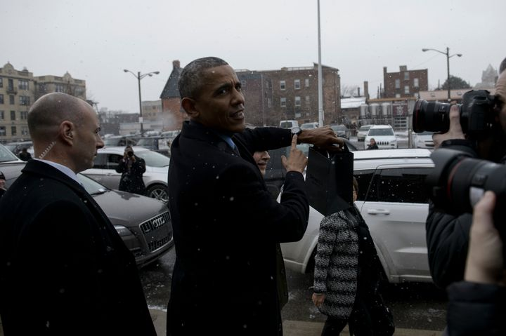 US President Barack Obama points to his Shinola watch, which he already owned, after visiting a Shinola store January 20, 2016 in Detroit, Michigan.