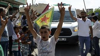 Kurdish people show v-signs and chant slogans along the road as the convoy carrying the body of US citizen Keith Broomfield killed in fighting with militants of the Islamic State group in Kobani, Syria, is driven by through Suruc, on the Turkey-Syria border, on June 11, 2015. Broomfield, 20, from Massachusetts, died on June 3 in a Syrian village near Kobani, making him likely the first US citizen to die fighting alongside Kurds against the Islamic State group. AFP PHOTO/BULENT KILIC        (Photo credit should read BULENT KILIC/AFP/Getty Images)