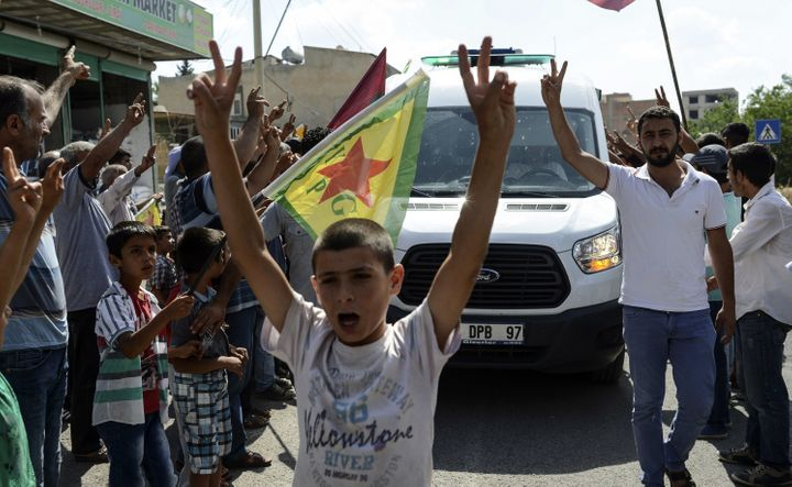 Kurdish people show v-signs and chant slogans along the road as the convoy carrying the body of US citizen Keith Broomfield k