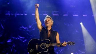 Singer Jon Bon Jovi raises his hand during a performance with his band Bon Jovi in concert at Gelora Bung Karno stadium in Jakarta, Indonesia, September 11, 2015.  REUTERS/Nyimas Laula