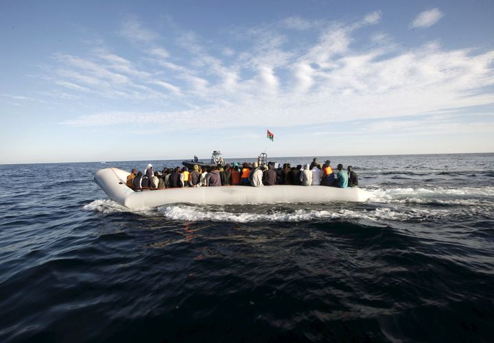 Migrants, who tried to flee to Europe, travel in a dinghy after they were stopped by Libyan coast guards and made to head to