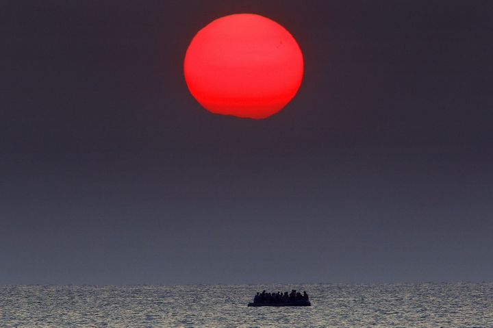 A red sun is seen over a dinghy overcrowded with Syrian refugees drifting in the Aegean sea between Turkey and Greece after i