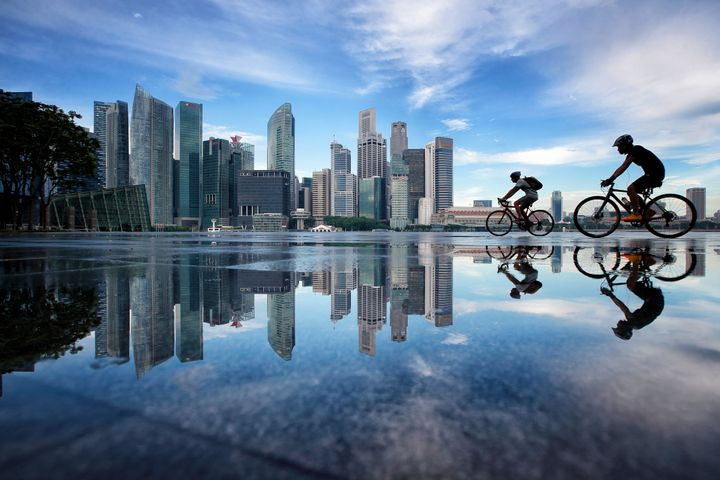 People cycle along Marina Bay with the Singapore Central Business District skyline in the background on November 2, 2016 in S
