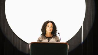 Speaker at podium backlit with white light