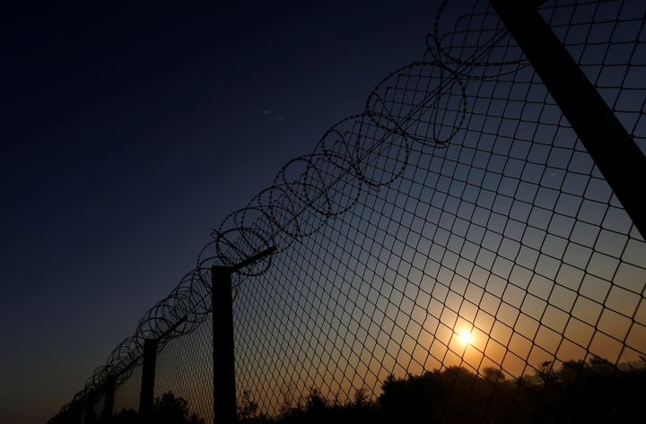 The sun rises along the Hungary and Serbia border fence near the village of Asotthalom, Hungary, October 2, 2016.