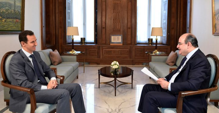 Syria's President Bashar al-Assad (L) attends an interview with al-Watan newspaper in Damascus, Syria, in this handout pictur