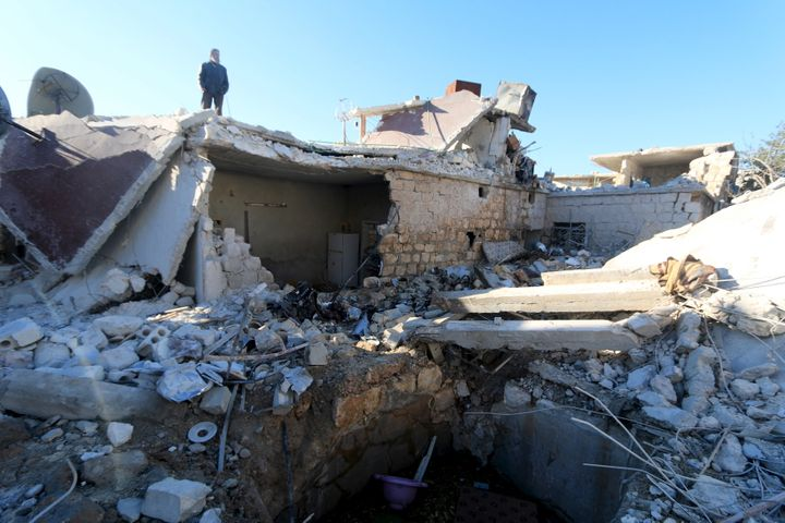 A man inspects a site hit by what residents said were airstrikes carried out by the Russian air force in the town of Turmanin