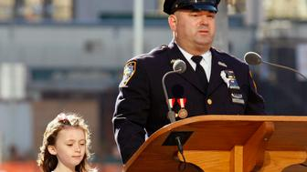New York police officer James Smith reads the names of victims during a ceremony to mark the fifth anniversary of the September 11 attacks at the site of the World Trade Center as his daughter Patricia stands by him, in New York September 11, 2006. Moira Smith, wife and mother to the couple, was a police officer killed in the attacks.      REUTERS/Shaun Best    (UNITED STATES)