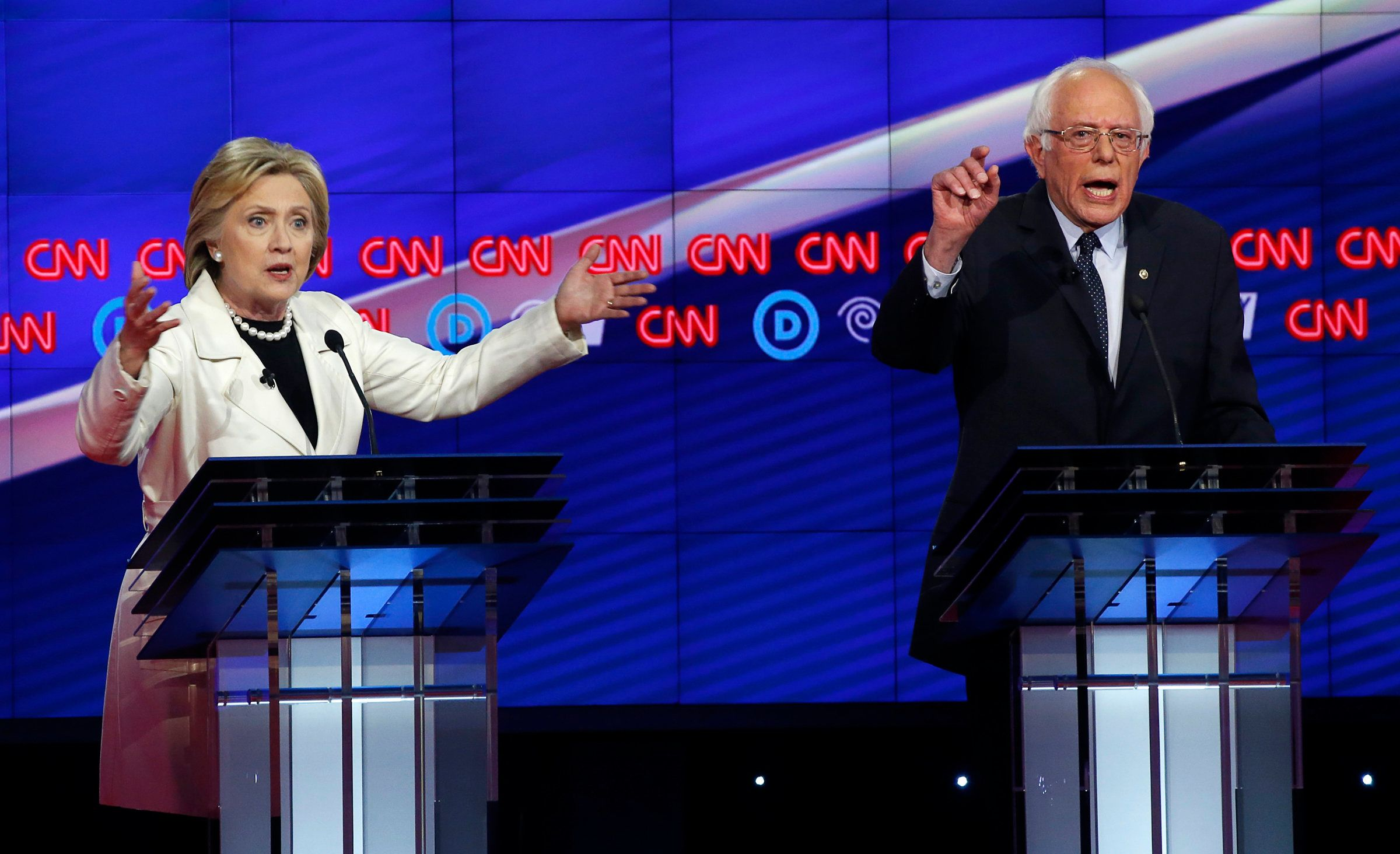 Democratic U.S. presidential candidates Hillary Clinton (L) and Senator Bernie Sanders speak simultaneously during a Democratic debate hosted by CNN and New York One at the Brooklyn Navy Yard in New York April 14, 2016.   REUTERS/Lucas Jackson