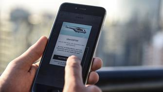 A passenger uses the Uber Technologies Inc. UberCopter application on a smart phone to order a flight in Sao Paulo, Brazil, on Friday, June 17, 2016. The San Francisco-based ride-hailing company has chosen the congested Sao Paulo financial hub of 20 million people to test its helicopter service. Photographer: Paulo Fridman/Bloomberg via Getty Images