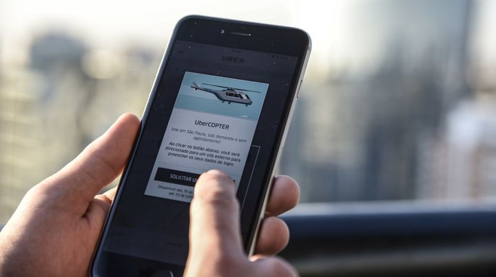passenger uses the Uber Technologies Inc. UberCopter application on a smart phone to order a flight in Sao Paulo, Brazil, on