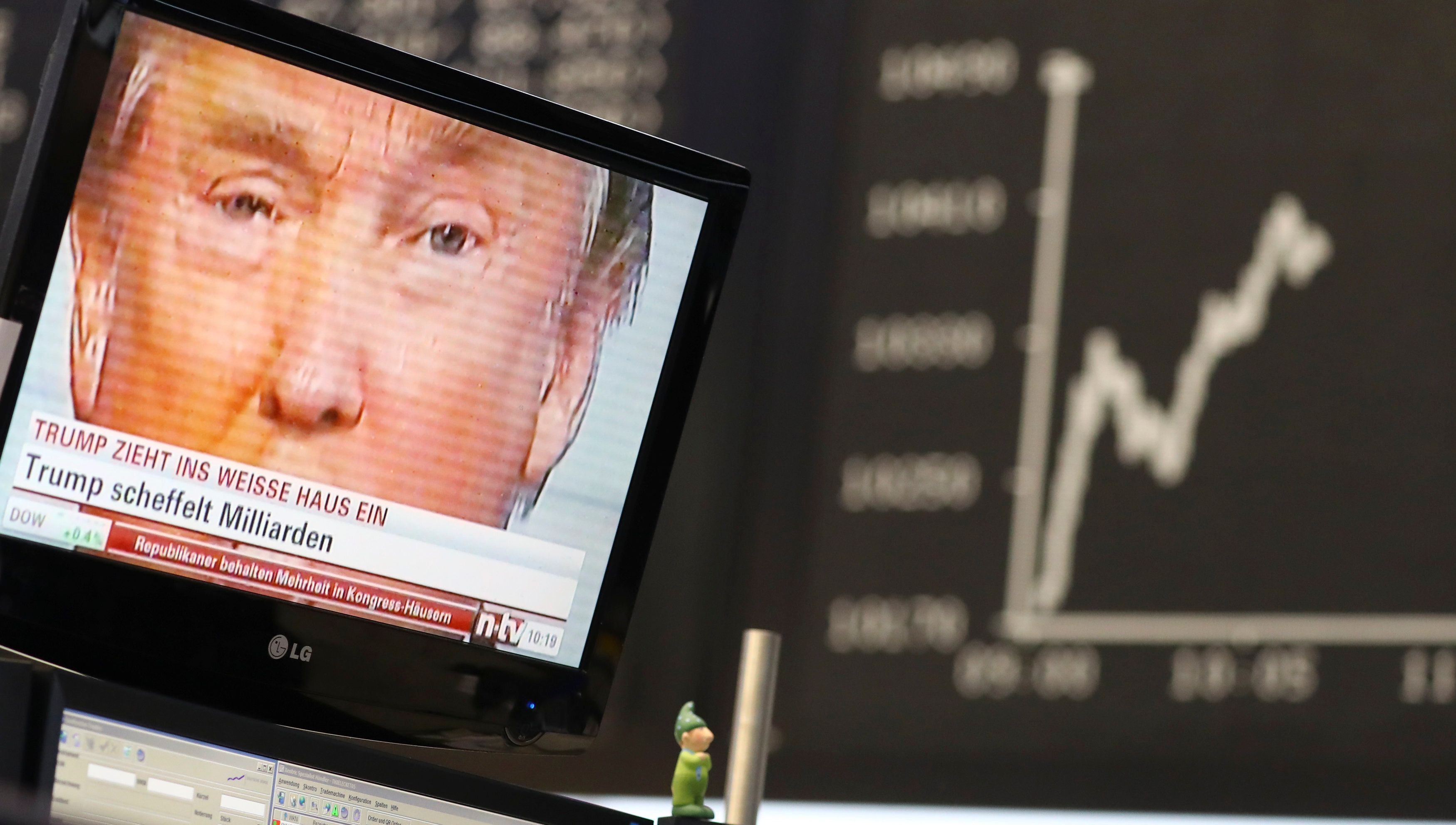 A TV screen showing U.S. President-elect Donald Trump is pictured in front of the German share price index, DAX board, at the stock exchange in Frankfurt, Germany, November 9, 2016. REUTERS/Kai Pfaffenbach