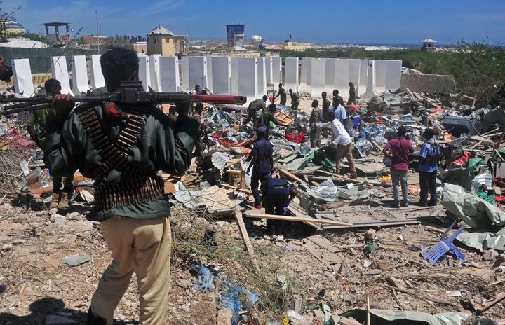 Civilians and soldiers stand amongst scattered objects and belongings at the scene of a car bomb attack near the Peace Hotel