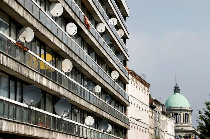 Television satellite dishes are pictured on an apartment building in the Brussels district of Molenbeek, Belgium, August 14,