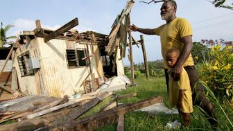 TOPSHOT - A man named Ikavatu from the village of Namena in Tailevu gestures towards his damaged house after Cyclone Winston swept through the area. The death toll from super-cyclone Winston jumped to 42 on February 24 as concerns grew for remote Fijian villages still waiting for help after the most powerful storm in the Pacific nation's history.   AFP PHOTO / STEVEN SAPHORE / AFP / STEVEN SAPHORE        (Photo credit should read STEVEN SAPHORE/AFP/Getty Images)