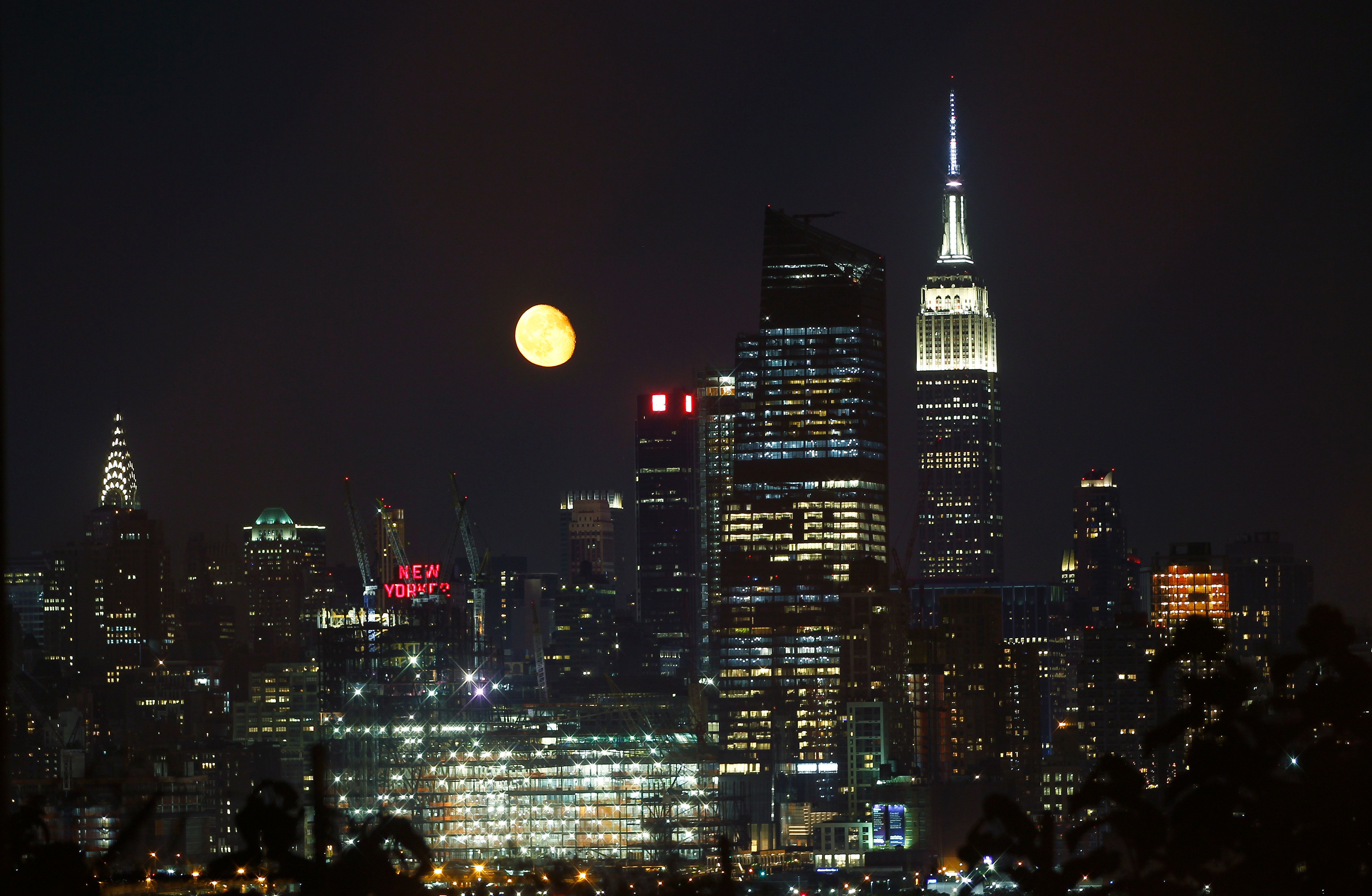 NEW YORK, NY - JULY 22: The moon rises between the Chrysler Building and the Empire State Building on July 22, 2016 in New York City. (Photo by Gary Hershorn/Getty Images)