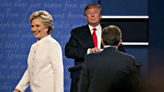 Donald Trump, 2016 Republican presidential candidate, stands as Hillary Clinton, 2016 Democratic presidential candidate, exits the stage after the third presidential debate in Las Vegas, Nevada, U.S., on Wednesday, Oct. 19, 2016. Donald Trump is trying another wild-card play in the third and final presidential debate with Hillary Clinton in perhaps his last chance to reverse his campaign's spiral and halt his Democratic rival's rising electoral strength. Photographer: Daniel Acker/Bloomberg via Getty Images