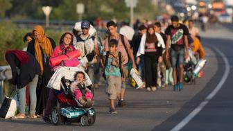 BUDAPEST, HUNGARY - SEPTEMBER 04:  Migrants begin walking towards the Austrian border on September 4, 2015 in Bicske, near Budapest, Hungary. Several thousand migrants began walking today towards Austria after all international trains to Western Europe remained cancelled.  (Photo by Matt Cardy/Getty Images)