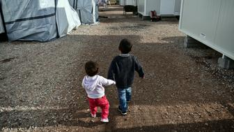 Children walk  at the Ritsona refugee camp, north of Athens, on December 21, 2016. There are over 60,000 refugees and migrants trapped in Greece after EU and Balkan countries further north shut their borders in March. / AFP / Louisa GOULIAMAKI        (Photo credit should read LOUISA GOULIAMAKI/AFP/Getty Images)