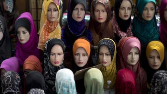 This picture taken on November 30, 2012 shows mannequins with the latest styles of headscarfs or 'hijab' on display outside a shop in downtown Kuala Lumpur. A Malaysian 'hijab', also called a tundung, is a head covering or scarf a woman can wear in public as a symbol of her religious devotion. Tudung is the main dress code for Muslim women in Malaysia, Indonesia, the southern provinces in Thailand, Singapore and Brunei.  The peak in sale of tudungs is during the month of Ramadan.   AFP PHOTO / Saeed KHAN        (Photo credit should read SAEED KHAN/AFP/Getty Images)