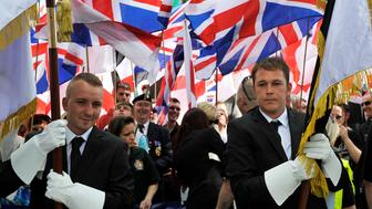 LUTON, UNITED KINGDOM - JUNE 27: British First group members seen during protest march with banners and flags at Bury Park on June 27, 2015 in Luton, England.  The far-right group marched from the train station and finished opposite Bute Street car park whilst a counter demonstration was held outside the Hat Factory. At the end of the march both of Britain First's leaders, Paul Golding and Jayda Fransen, gave speeches.  PHOTOGRAPH BY Tony Margiocchi / Barcroft Media (Photo credit should read Tony Margiocchi / Barcroft Media via Getty Images)