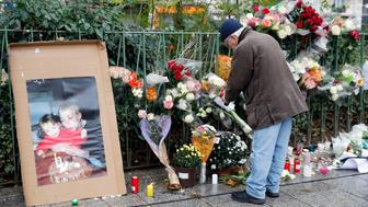 PARIS, FRANCE - NOVEMBER 13:  A man puts a flower near the Bataclan concert hall where flowers were laid, after a ceremony marking the first anniversary of the Paris terror attacks on November 13, 2016 in Paris, France. France pay tributes to the victims of the 2015 Paris terrorists attacks which left at least 130 dead and many others injured by gunmen and suicide bombers from the Islamic State.  (Photo by Chesnot/Getty Images)