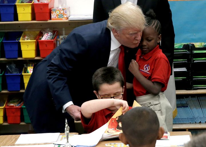 Republican presidential nominee Donald Trump hugs a student after receiving a bible as a gift during a campaign visit to Inte