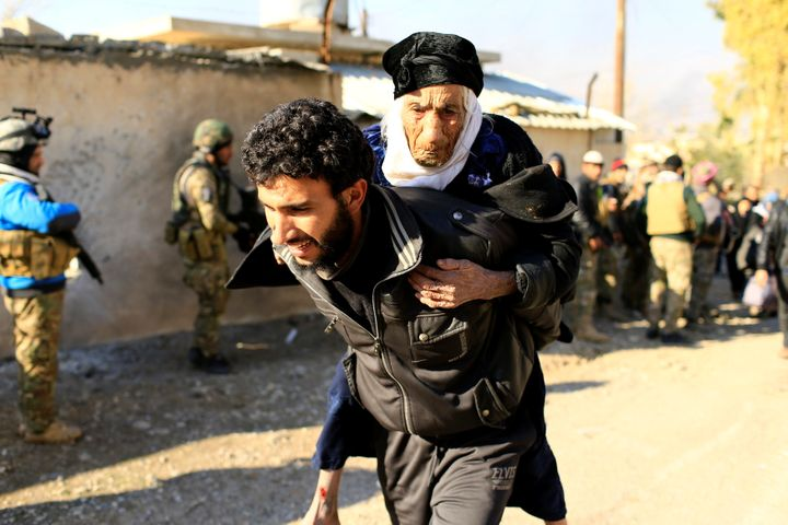 A displaced man, who fled the Islamic State stronghold of Mosul, carries a woman in the Mithaq district of eastern Mosul, Ira