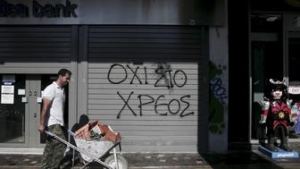 "Graffiti on a closed Attica Bank branch reads ""No to the debt"" as a worker pushing a cart walks by in Athens, Greece July 13, 2015. REUTERS/Alkis Konstantinidis/File photo"