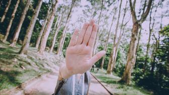 Young Asian female gesturing stop sign in the nature encouraging the public to protect natural environment and natural resources.