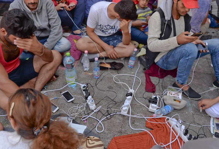A group of Migrants charging their phones as they awaiting for the train to Austria and Germany at Budapest Keleti railway st
