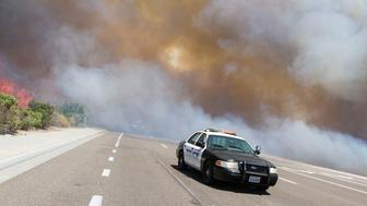CARLSBAD, CA - MAY 14:  A Carlsbad Police vehicle drives south on El Camino Real as the Poinsettia Fire jumps the road moving west on May 14, 2014 in Carlsbad, California. Thirty homes have burned in the fast-moving Carlsbad blaze, fueled by record heat, high winds and dry conditions. At least four other fires advanced in nearby communities.  (Photo by Daniel Knighton/Getty Images)