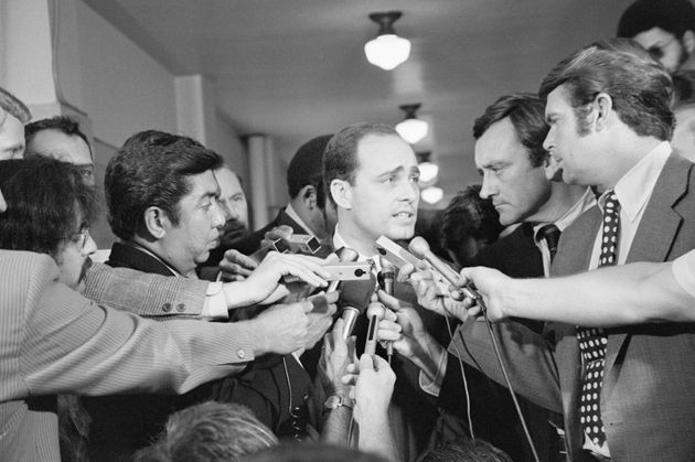 A crowd of reporters surround Los Angeles prosecutor Vincent Bugliosi as he leaves the courtroom in the...