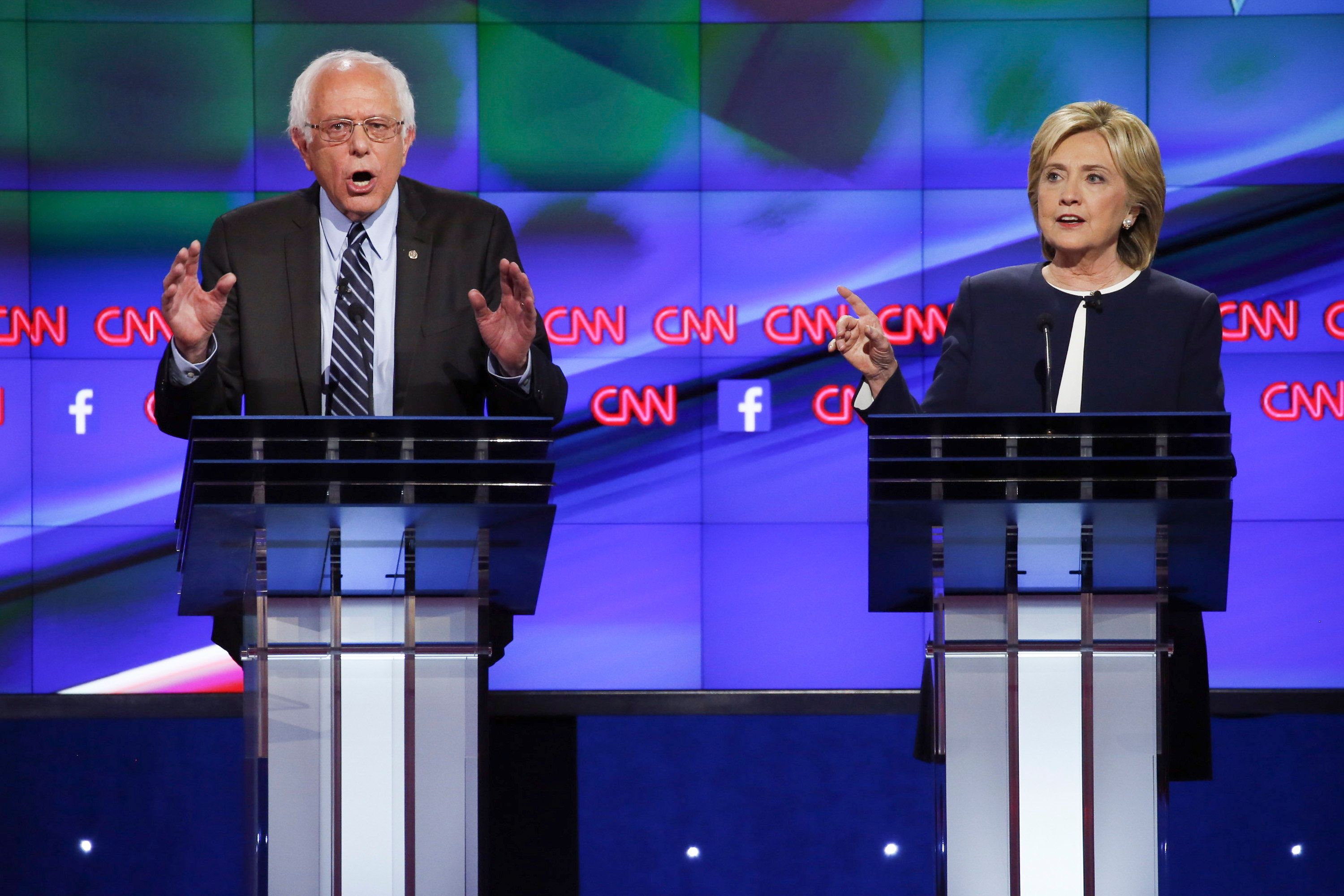 Senator Bernie Sanders, an independent from Vermont, left, and Hillary Clinton, former U.S. secretary of state, participate in the first Democratic presidential debate at the Wynn Las Vegas resort and casino in Las Vegas, Nevada, U.S., on Tuesday, Oct. 13, 2015. While tonight's first Democratic presidential debate will probably lack the name-calling and sharp jabs of the Republican face-offs, there's still potential for strong disagreements between the party's leading contenders. Photographer: Josh Haner/Pool via Bloomberg