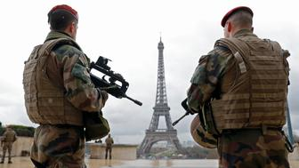 French army paratroopers patrol near the Eiffel tower in Paris, France, March 30, 2016 as France has decided to deploy 1,600 additional police officers to bolster security at its borders and on public transport following the deadly blasts in Brussels.  REUTERS/Philippe Wojazer