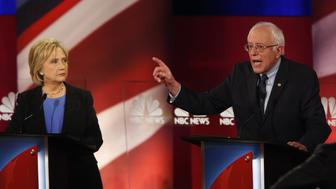 Hillary Clinton, former Secretary of State and 2016 Democratic presidential candidate, left, looks on as Senator Bernie Sanders, an independent from Vermont and 2016 Democratic presidential candidate, speaks during the Democratic presidential candidate debate in Charleston, South Carolina, U.S., on Sunday, Jan. 17, 2016. Hours before Sunday's Democratic debate, the two top Democratic contenders held a warm-up bout of sorts in multiple separate appearances on political talk shows, at a time when the polling gap between the pair has narrowed in early-voting states. Photographer: Patrick T. Fallon/Bloomberg via Getty Images
