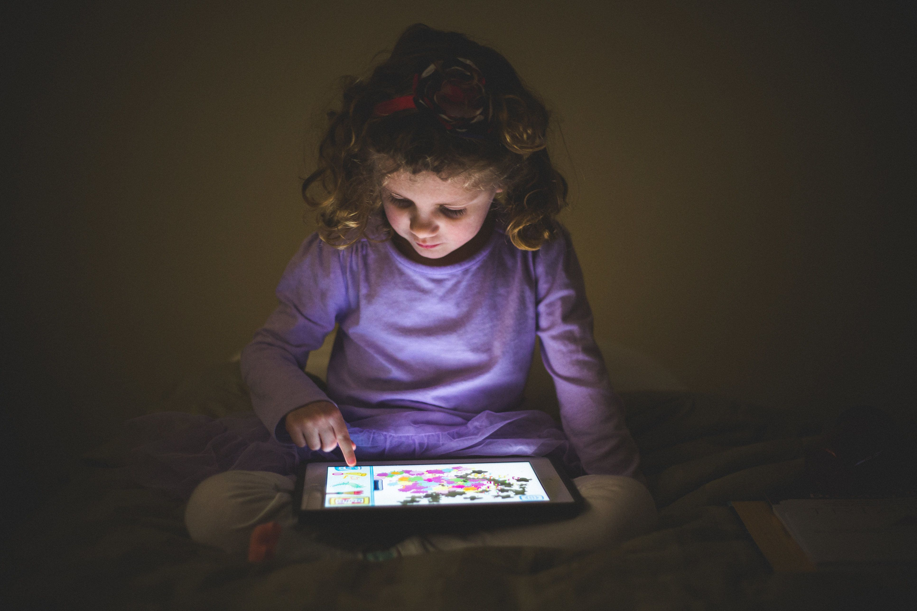 Little girl plays with a digital tablet in a dark room, the light from the screen illuminates her face.