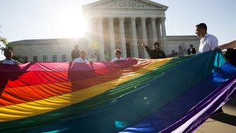 Gay marriage supporters hold a gay rights flag in front of the Supreme Court before a hearing about gay marriage in Washington April 28, 2015. The nine justices will be hearing arguments concerning gay marriage restrictions imposed in Kentucky, Michigan, Ohio and Tennessee, four of the 13 states that still outlaw such marriages.    REUTERS/Joshua Roberts