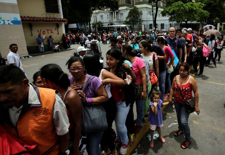 Venezuelans stand in line as they wait to buy essential items and basic food outside of a supermarket in Caracas, Venezuela o