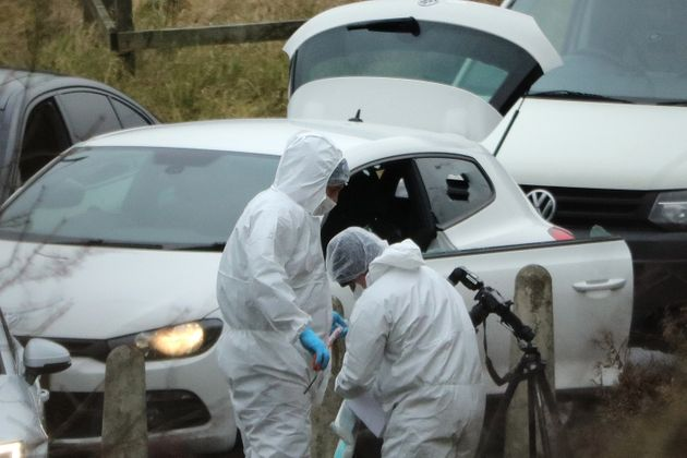 Police forensics officers examine a silver Audi with bullet holes in its windscreen near junction J24...