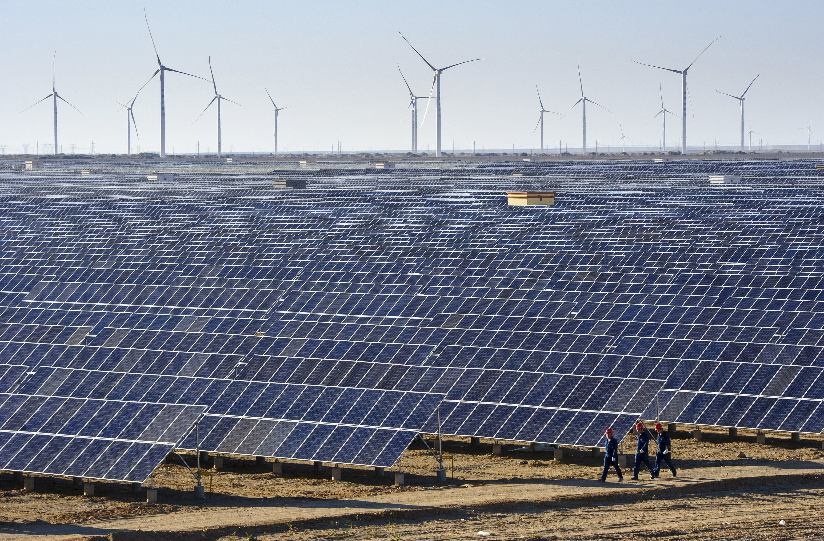 Workers walk past solar panels and wind turbines at a power plant in Hami, Xinjiang Uighur Autonomous Region, China.