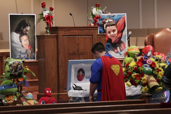 Dale Hall, dressed in a Superman outfit, stands before the casket during the funeral for his brother 6-year-old Jacob Hall at