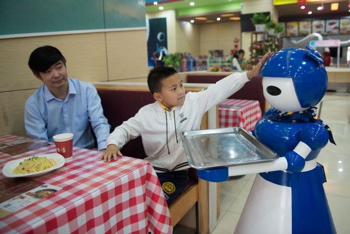 Robot waiters working at a robot restaurant. Kunshan, China. May 22, 2016.