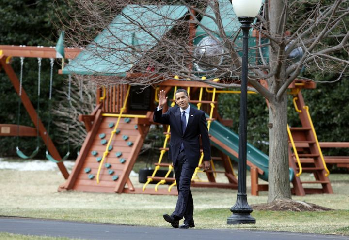 President Barack Obama walks past his daughters' swing set shortly after it was installed in 2009.